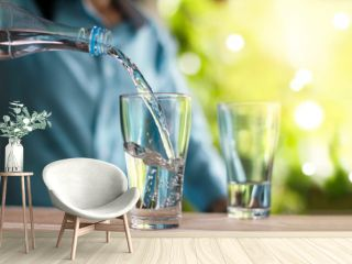 Woman's hand pouring drinking water from bottle to the glass on wooden table, green nature background
