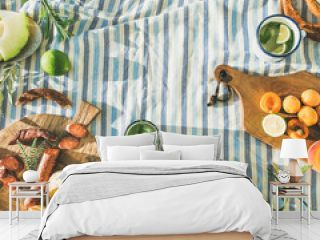 Flat-lay of summer picnic set with fruit, cheese, sausage, bagels and lemonade over striped blanket, top view, copy space, square crop