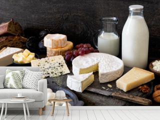 Cheese, milk and dairy products on rustic dark wood and slate background.