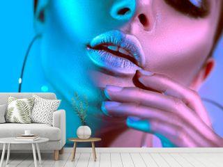 High fashion model woman in colorful bright neon lights posing in studio. Beautiful sexy girl, trendy glowing makeup, metallic silver lips