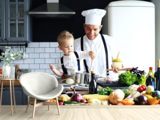 Dad and little son are cooking dinner