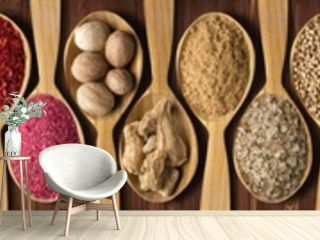 spices in wooden spoons on black table. set of condiments and herbs for decorating website headers or packs with food.