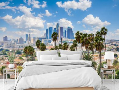 Beautiful cloudy day of Los Angeles downtown skyline and palm trees in foreground
