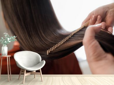 Close up of hairstyle master hands combing long hair with special hairbrush