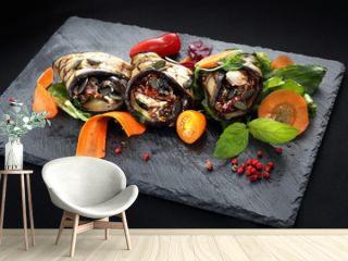 Warzywne roladki. Roladki z grillowanego bakłażana z suszonymi pomidorami i serem podane na sałacie i marchewce.