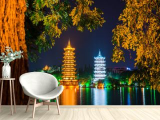 Night view of the Sun and Moon Pagodas at Shanhu Lake or Fir Lake. Gold and Silver Pagodas locate at downtown of Guilin, China. Guilin is a popular tourist destination of Asia.