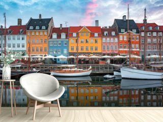 Nyhavn at sunrise, with colorful facades of old houses and old ships in the Old Town of Copenhagen, capital of Denmark.