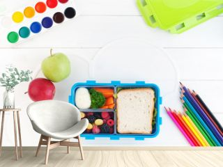 Open lunch box on the white wooden background with copy space