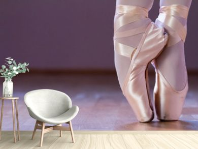 Feet dressing a pair of pointe shoes