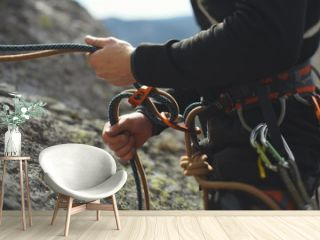 Easy belay-descender device in the hands of a climber closeup. Climbing gear and equipment.