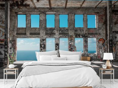 Abandoned  factory ruin  / warehouse loft with windows and ocean and blue sky background