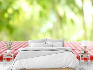 Empty table with checkered red napkin on green blurred background. Space for design