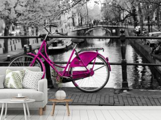 A picture of a lonely pink bike on the bridge over the channel in Amsterdam. The background is black and white.