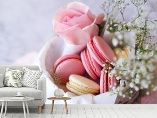 Beautiful colourful macarons with flowers in round paper box, closeup