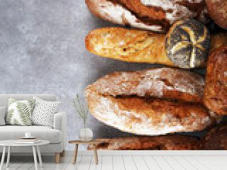 Assortment of baked bread and bread rolls on stone table background