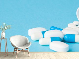 Close up pills spilling out of pill bottle on blue background. Medicine, medical insurance or pharmacy concept