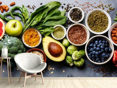 Healthy food clean eating selection: fruit, vegetable, seeds, superfood, cereal, leaf vegetable on gray concrete background