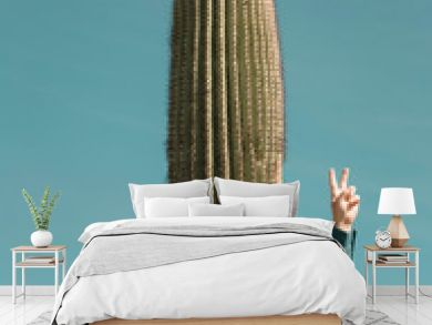 A man stands behind a cactus with his hand in the air giving a peace sign