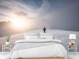 Man mountaineer walking with snow footprint on peak ridge