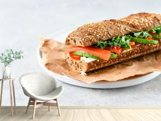 sandwich from a cereal baguette with avocado, salmon, cream cheese, tomatoes and lettuce leaves on a white plate.  light background, selective focus and copy space