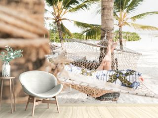 Woman relaxing in a hammock on a white sand beach in zanzibar