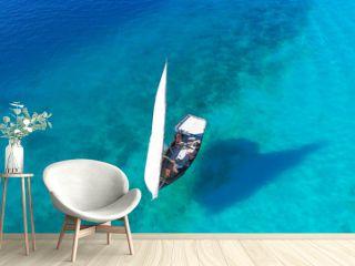 White sailboat in a sea of traditional Dhow Zanzibar island Nungwi Beach. Aerial view