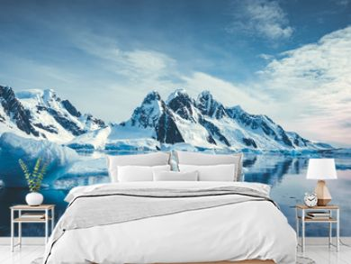 Blue Ice covered mountains in south polar ocean. Winter Antarctic landscape. The mount's reflection in the crystal clear water. The cloudy sky over the massive rock glacier. Travel wild nature