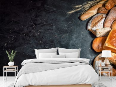 Assortment of fresh baked bread on dark background. White and rye bread, buns with copy place