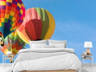 Three multi colored hot air balloons flying close to each othe over blue sky