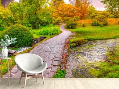 enchanted eden garden bridge over pond in horizontal panoramic Nymph Garden or Giardino della Ninfa in Lazio - Italy