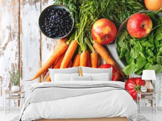 Variety of fresh fruits, vegetables and berries carrot, spinach, tomatoes, red apples, blueberries over white plank wooden background. Flat lay, space