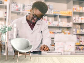 Portrait of a happy African American pharmacist writing prescription at workplace in modern pharmacy