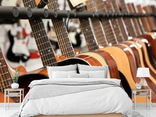Row of different guitars in music store, closeup