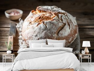 Fresh loaf of bread with salt on wooden table