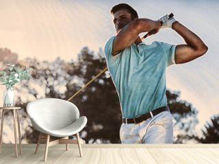 Full length of handsome golfer man taking shot