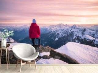 Young woman in snowy mountains at sunset in winter. Beautiful slim girl on the mountain peak against snow covered rocks and colorful red sky with clouds in the evening. Travel in Dolomites. Tourism