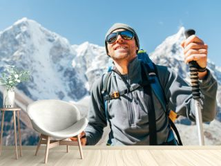Portrait of smiling Hiker man on Taboche 6495m and Cholatse 6440m peaks background with trekking poles, UV protecting sunglasses. He enjoying mountain views during Everest Base Camp trekking route.