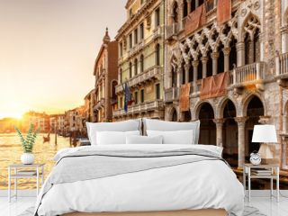 Venice at sunset, Italy. Ca' d'Oro palace (Golden House) in foreground. It is landmark of Venice. Beautiful view of Grand Canal in the Venice center at dusk. Scenery of the old Venice city in evening.