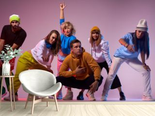 Active group of modern style dancers demonstrating different gestures, young beard man in yellow cap showing tongue looking at camera, sport and urban culture concept