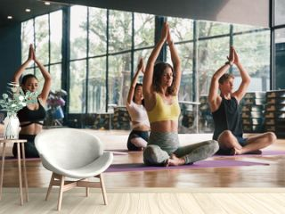 Group of young people practicing yoga In the prayer position and raised hands while sitting on mat at gym, Concept of relaxation and meditation