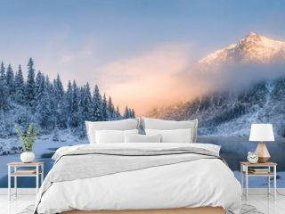 Sunrise in winter mountains. Mountain reflected in ice lake in morning sunlight. Amazing panoramic nature landscape in mountain valley.