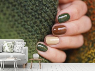 Autumn colors manicure on short round natural nails with green knitted scarf