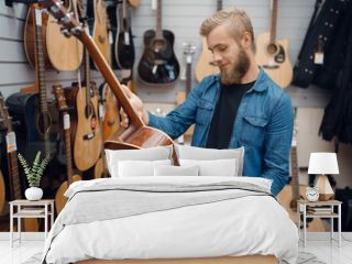 Bearded young man choosing a guitar in music store