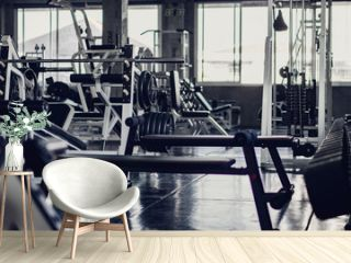 interior background of room in gym or fitness center fully equip of bodybuilding equipments and machines