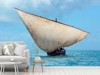 Wooden sailboat (dhow) on the open sea with clouds, Zanzibar.