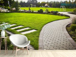 Landscaping of the garden. path curving through Lawn with green grass and walkway tiles.