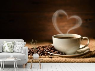 Cup of coffee with heart shape smoke and coffee beans on burlap sack on old wooden background