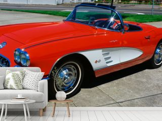 This is a restored 1959 Corvette. It is bright red with a white side panel with white sidewall tires. The convertible top is down. It is parked on flat pavement.