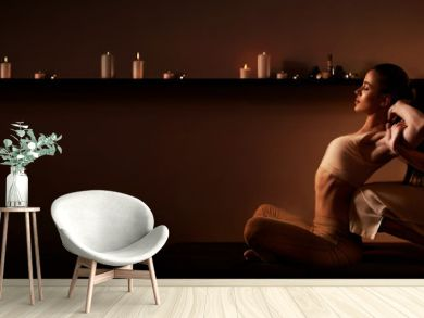 Young fit woman has Thai massage at luxury spa. Warm inviting colors, calm atmosphere, charming light. Copy space