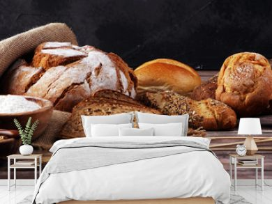Assortment of baked bread and bread rolls and cutted bread on table background